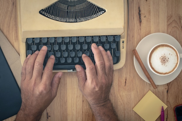 Main utilise des machines à écrire vintage sur table en bois Photo Premium