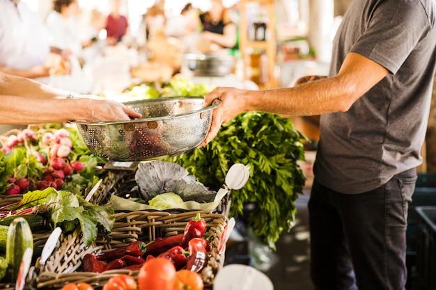 Main de vendeur tenant un récipient en acier inoxydable pendant qu'un client achète des légumes au marché Photo gratuit