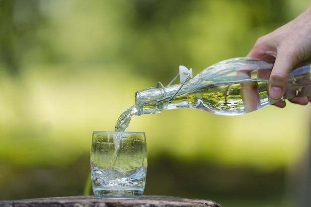 Main verser de boire de l'eau de bouteille en verre avec fond naturel Photo Premium
