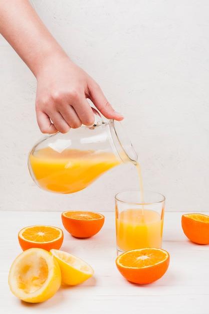 Main, verser, jus orange, dans, verre Photo gratuit