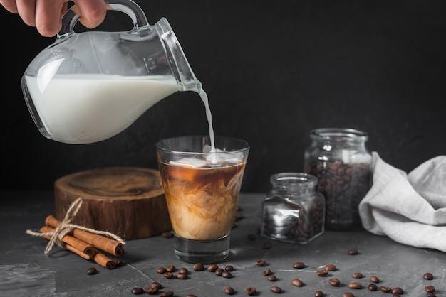 Main Verser Le Lait Dans Un Verre Avec Du Café Photo gratuit