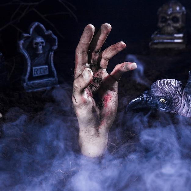 Main de zombie et corbeau effrayant au cimetière d'halloween Photo gratuit
