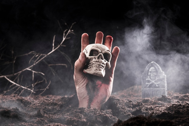 Main de zombie d'halloween tenant le crâne au cimetière Photo gratuit