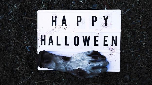 Main de zombie avec panneau sur un terrain forestier Photo gratuit