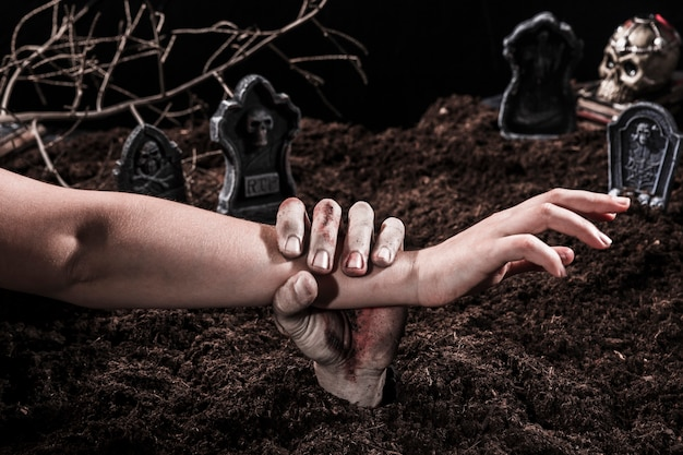Main de zombie tenant le bras d'une personne au cimetière d'halloween Photo gratuit