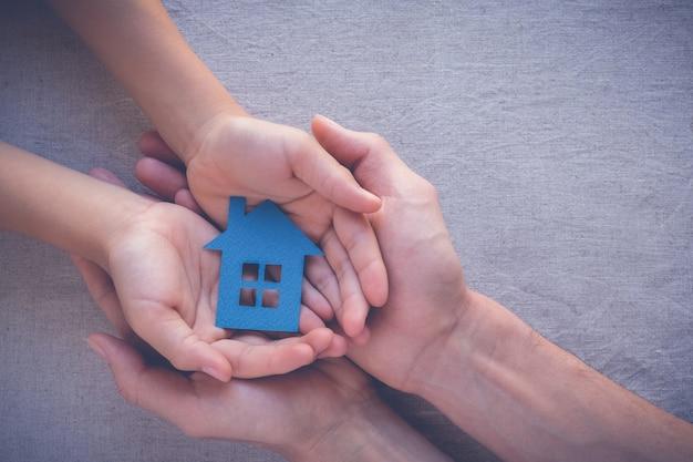 Mains d'adulte et d'enfant tenant la maison de papier, concept de maison familiale et de l'immobilier Photo Premium