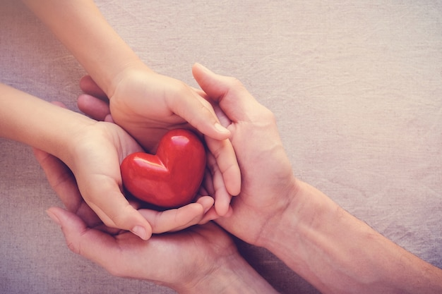 Mains adultes et enfants holiding coeur rouge, soins de santé amour, donner, espoir et concept de famille Photo Premium