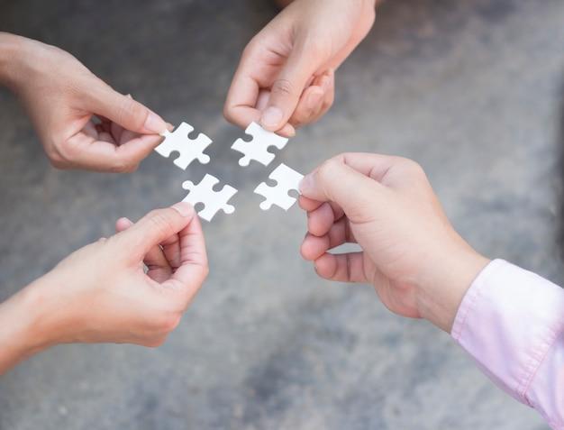 Mains d'affaires sur le concept de travail d'équipe de puzzle Photo Premium