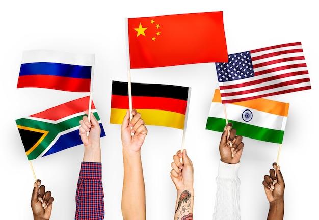 Mains agitant des drapeaux de chine, d'allemagne, d'inde, d'afrique du sud et de russie Photo gratuit