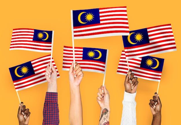 Mains agitant des drapeaux de malaisie Photo gratuit