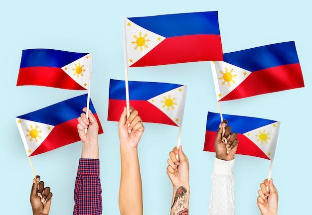 Mains agitant des drapeaux des philippines Photo gratuit