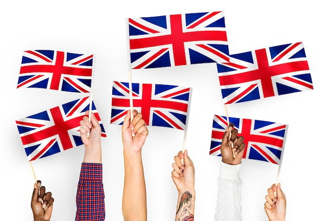 Mains agitant le union jack Photo gratuit