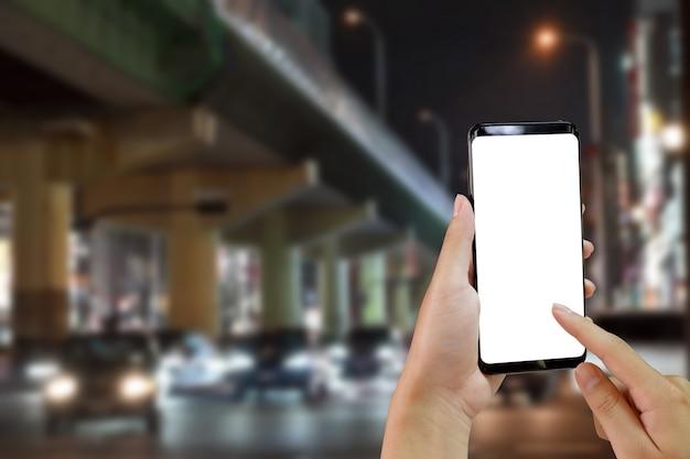 Mains à l'aide de maquette de téléphone portable sur la route avec les transports en ville pendant la nuit. Photo Premium