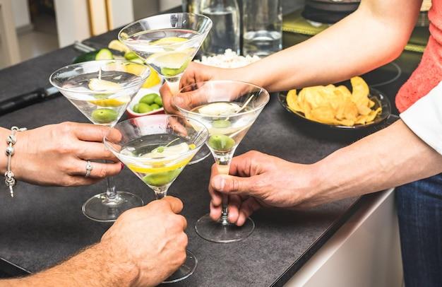 Mains d'amis s'amusant à la fête à la maison avec apéritif buvant des cocktails martini Photo Premium