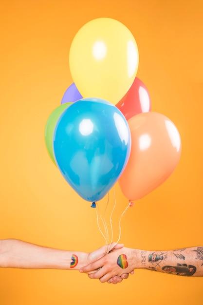 Mains avec des ballons colorés Photo gratuit