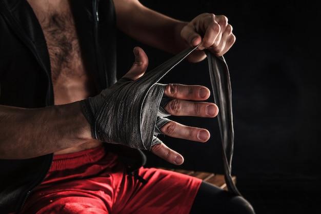 Les Mains Avec Un Bandage De Kickboxing Formation Homme Musclé Sur Fond Noir Photo gratuit