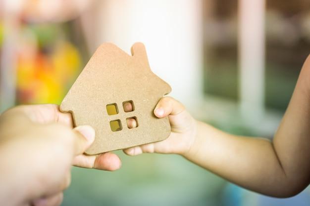 Mains de bébé tenant un modèle de maison avec la main de la mère. Photo Premium