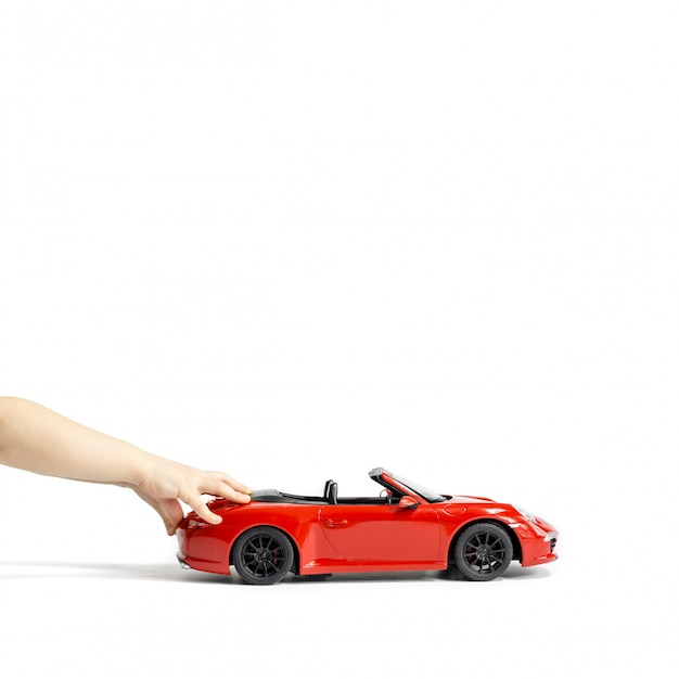 Mains de bébé sur la voiture de jouet rouge isolée sur fond blanc. espace de copie Photo Premium