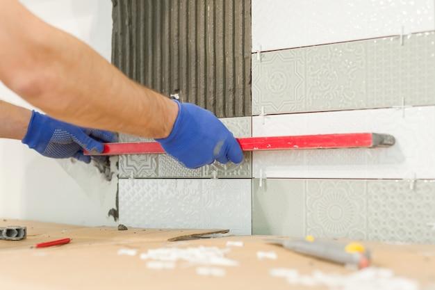 Mains de carreleur installer des carreaux de céramique sur le mur Photo Premium