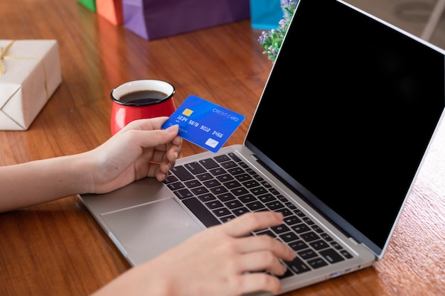 Mains avec carte de crédit hold utilisant un ordinateur portable pour l'e-marketing ou le concept de magasinage en ligne Photo Premium