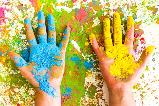 Mains en couleurs bleu et jaune sur des couleurs vives et sèches Photo gratuit