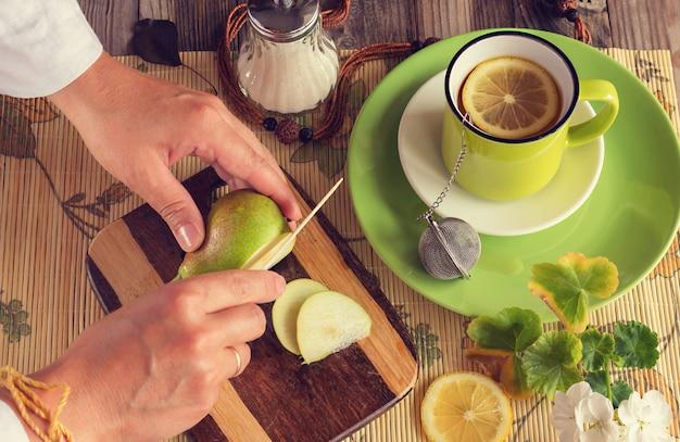 Les mains coupent une poire. ensuite, thé au citron dans une tasse verte, un sucrier, une planche avec une poire verte et un couteau. photo atmosphérique. couleurs vives fraîches. vue de dessus. Photo Premium