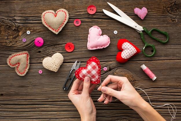 Mains cousant une forme de coeur rouge sur fond en bois Photo gratuit