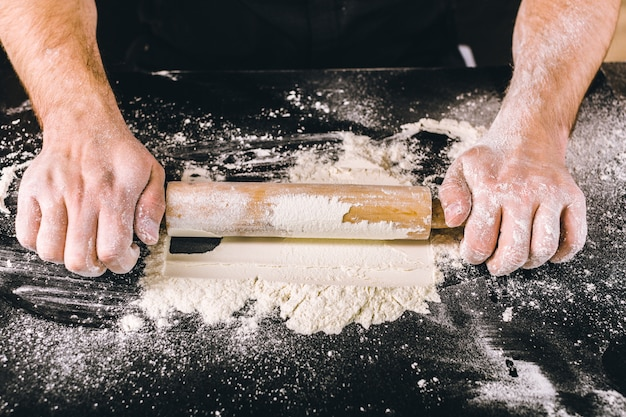 Mains cuisson de la pâte avec un rouleau à pâtisserie Photo Premium