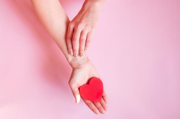Les Mains D'une Dame Tenant Un Coeur Sur Un Mur Rose, Saint Valentin Photo Premium