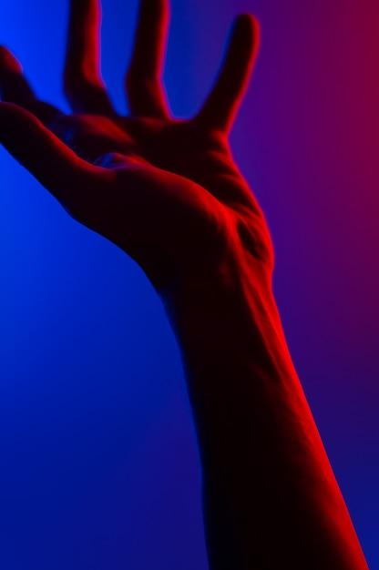 Mains dans le néon coloré contraste bleu rouge. Photo Premium
