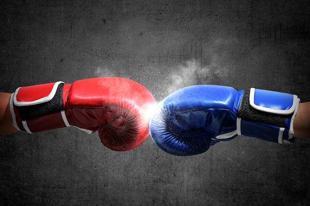 Les mains de deux hommes avec des gants de boxe bleus et rouges se sont cogné les poings Photo Premium