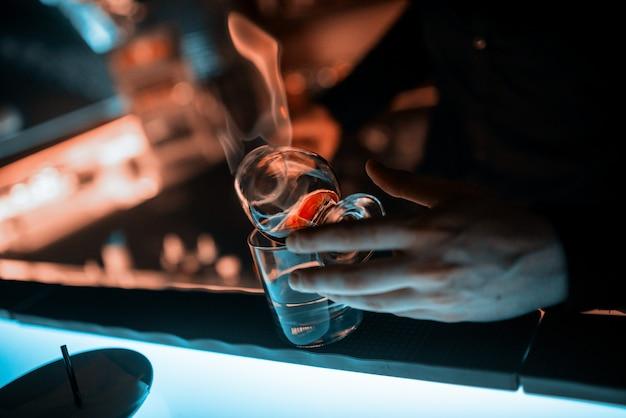 Les mains du barman, gobelet en verre sur le comptoir Photo Premium