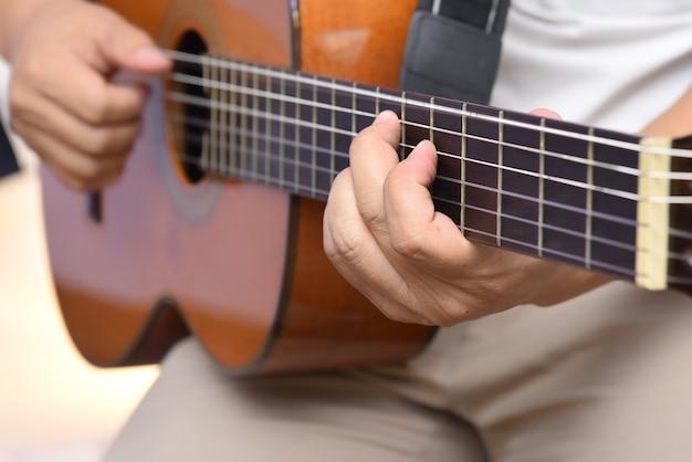 Mains du guitariste jouant une mélodie sur une guitare acoustique en bois à six cordes Photo Premium