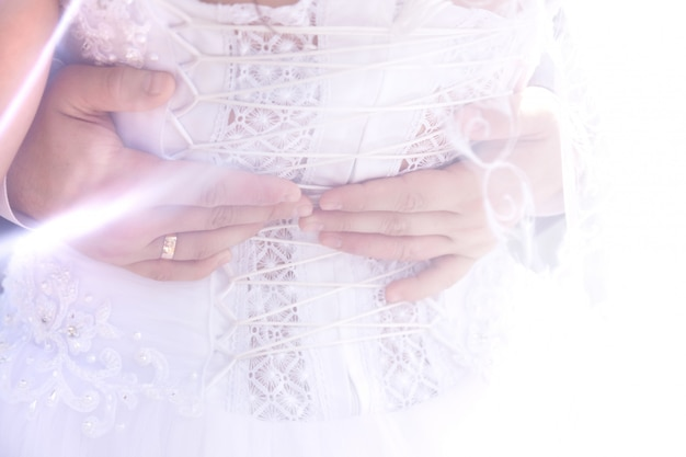 Les mains du marié sur le dos de la mariée à travers le voile Photo Premium