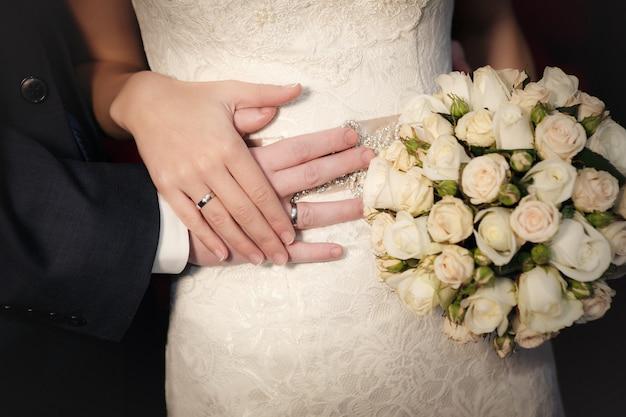 Mains du marié et de la mariée avec des alliances et un bouquet de mariée de roses Photo Premium