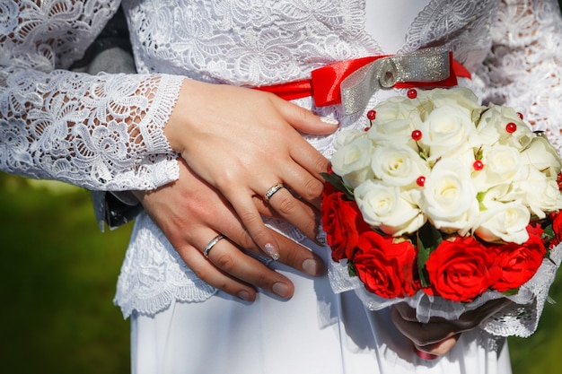 Mains du marié et de la mariée avec des alliances et un bouquet de roses beiges Photo Premium