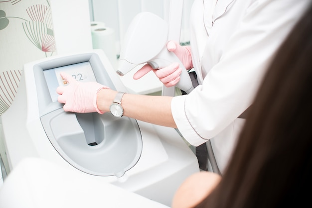 Les mains du médecin en gants roses tiennent l'appareil pour une épilation et appuient sur l'écran tactile. le concept de dispositif de contrôle, épilation au laser Photo Premium