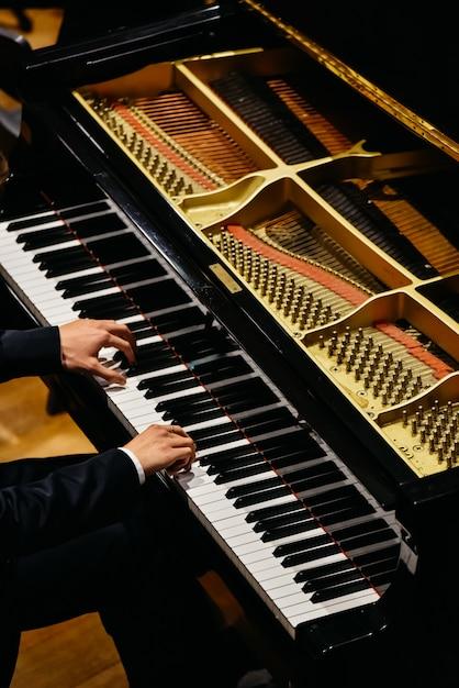 Mains du pianiste classique jouant du piano lors d'un concert. Photo Premium