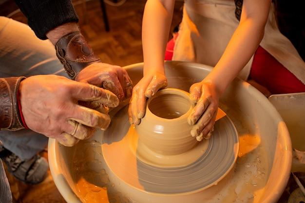 Les mains du potier et les mains de l'enfant travaillent avec de l'argile sur une machine spéciale Photo Premium