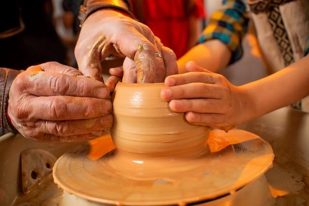 Les mains du potier et les mains de l'enfant travaillent avec de l'argile sur une machine spéciale. Photo Premium