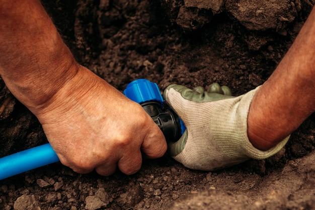Les mains du système d'irrigation fonctionnant avec un tuyau de raccordement Photo Premium