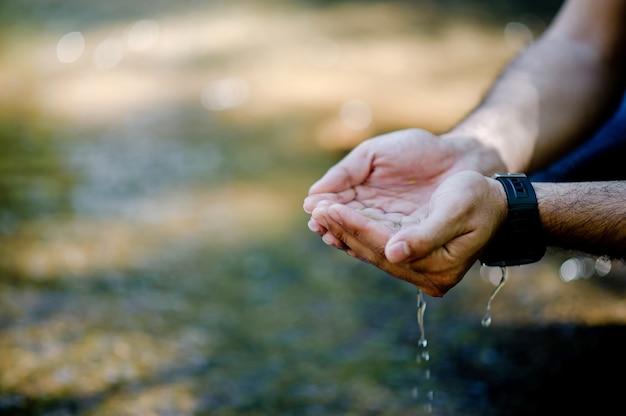 Mains et eau coulant des cascades naturelles Photo Premium