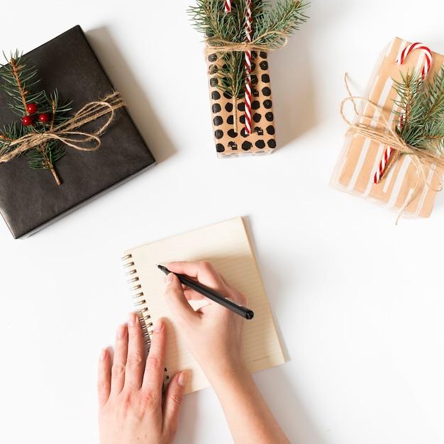 Mains écrivant dans un cahier avec des cadeaux emballés autour Photo gratuit