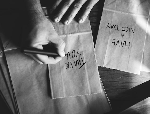 Mains écrivant des mots reconnaissants sur des sacs en papier Photo gratuit