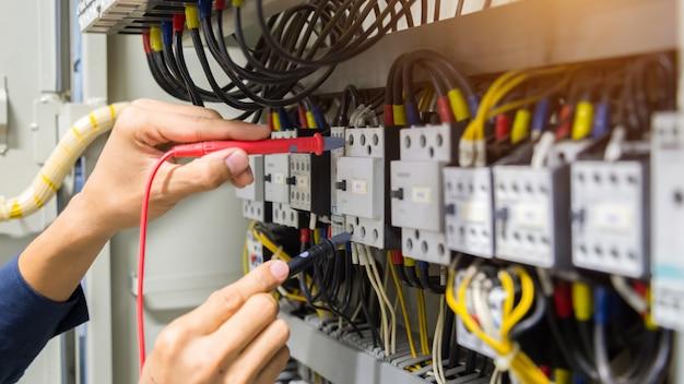 Mains d'électricien testant le courant électrique dans le panneau de commande. Photo Premium