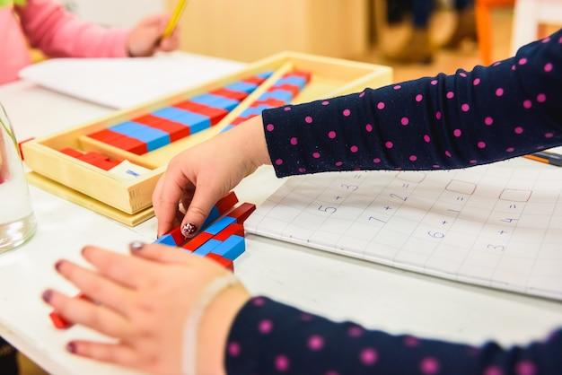 Mains d'un élève utilisant des matériaux en bois dans une école montessori. Photo Premium