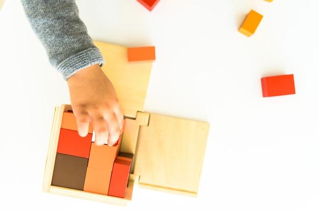 Mains de l'enfant, apprendre à monter des pièces dans un puzzle en bois 3d. Photo Premium