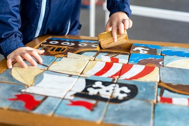 Les mains de l'enfant complètent un puzzle d'artisan composé de cubes en bois. Photo Premium