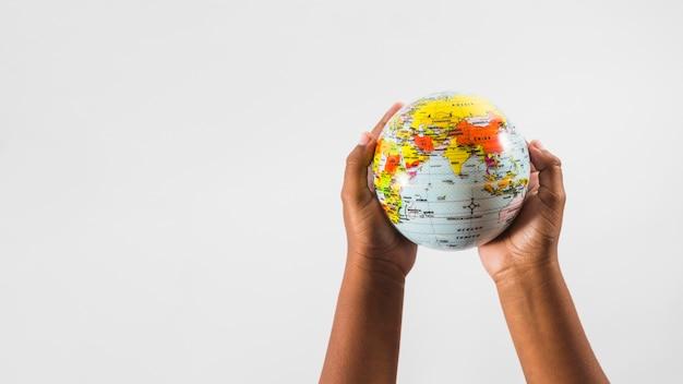 Mains d'enfant avec globe en studio Photo gratuit