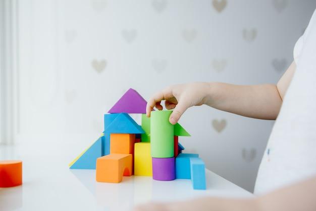 Mains d'enfant jouant avec des briques en bois colorées sur l'onglet blanc Photo Premium